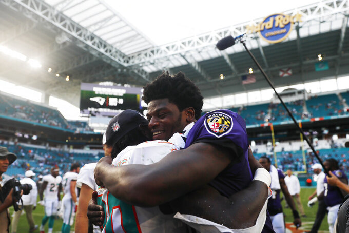 Baltimore Ravens quarterback Lamar Jackson (8) hugs Miami Dolphins defensive back Chris Lammons (30) at the end of an NFL football game, Sunday, Sept. 8, 2019, in Miami Gardens, Fla. The Ravens defeated the Dolphins 59-10. (AP Photo/Brynn Anderson)