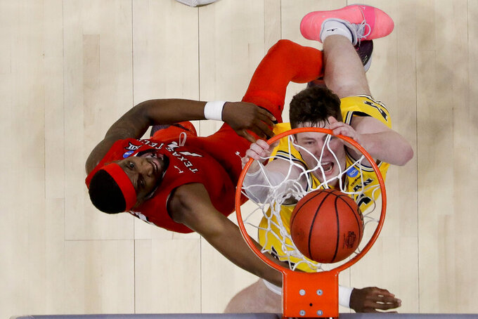 Michigan center Jon Teske, right, dunks past Texas Tech forward Tariq Owens during the second half an NCAA men's college basketball tournament West Region semifinal Thursday, March 28, 2019, in Anaheim, Calif. (AP Photo/Marcio Jose Sanchez)