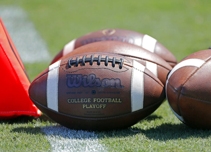 "FILE - In this Sept. 2, 2017, file photo, footballs sit on the turf ready for kick-off before the start of an NCAA football game between South Carolina and North Carolina State in Charlotte, N.C. A study from The Institute for Diversity and Ethics (TIDES) finds that white men still ""overwhelmingly"" fill leadership positions at top-level college sports programs and conferences, leaving a ""consistent underrepresentation of women and people of color"" in those roles. (AP Photo/Bob Leverone, File)"