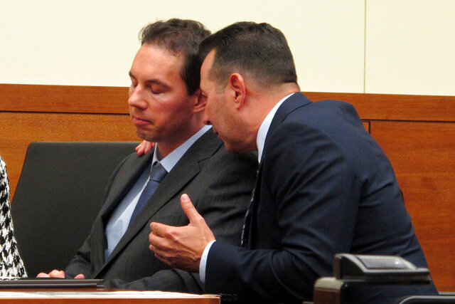 FILE - In this Aug. 28, 2019, file photo, defense attorney Jose Baez, right, talks to fired doctor William Husel during a court hearing in Columbus, Ohio. A judge has dismissed Husel's attempt to force Michigan-based Trinity Health Corporation and its insurer to cover the costs of his defense against murder charges in the deaths of 25 patients in the Columbus, Ohio-area, Mount Carmel Health System. Husel has pleaded not guilty. (AP Photo/Kantele Franko, File)