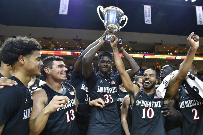 San Diego State celebrates with the tournament trophy after defeating Iowa in an NCAA college basketball game Friday, Nov. 29, 2019, in Las Vegas. (AP Photo/David Becker)