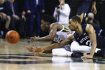 Baylor guard Davion Mitchell, left, reaches for a loose ball with Butler guard Aaron Thompson in the first half of an NCAA college basketball game, Tuesday, Dec. 10, 2019, in Waco, Texas. (AP Photo/Rod Aydelotte)