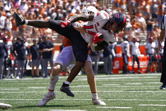 Texas Tech running back Xavier White (14) is stopped short of the end zone by Texas defensive back Brenden Schooler during the second half of an NCAA college football game on Saturday, Sept. 25, 2021, in Austin, Texas. (AP Photo/Chuck Burton)