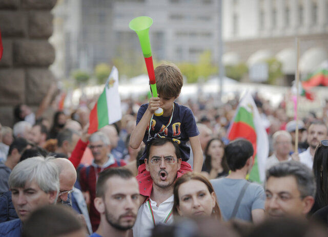 A father shouts slogans as he holds his son on his shoulders during a protest in front of the new National Assembly building, demanding government resignation in Sofia, Bulgaria, Tuesday, Sept. 22, 2020. Thousands of people took to the streets in cities across Bulgaria on Tuesday, Independence Day, calling on the prime minister and the chief prosecutor to step down over allegations they allowed an oligarchic mafia to seize control of the Balkan country. (AP Photo/Valentina Petrova)