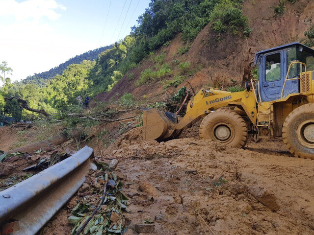 A bulldozer clears out the road damaged by landslide to access a village swamped by another landslide in Quang Nam province, Vietnam on Thursday, Oct. 29, 2020. Typhoon Molave slammed into Vietnam with destructive force Wednesday, sinking two fishing boats with 26 crew members in what was feared to be the most powerful storm to hit the country in 20 years. (Bui Van Lanh/VNA via AP)