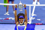 Naomi Osaka, of Japan, holds up the championship trophy after defeating Victoria Azarenka, of Belarus, in the women's singles final of the US Open tennis championships, Saturday, Sept. 12, 2020, in New York. (AP Photo/Frank Franklin II)