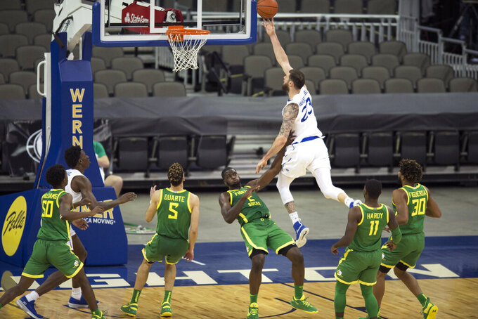 Oregon's Eugene Omoruyi (2) is knocked to the floor as he prevents Seton Hall's Sandro Mamukelashvili (23) from scoring during the second half of an NCAA college basketball game in Omaha, Neb., Friday, Dec. 4, 2020. (AP Photo/Kayla Wolf)