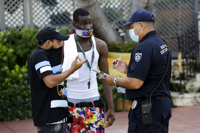 FILE - In this Friday, July 24, 2020 file photo, a man covers his nose with his shirt, left, as Luis Negron, a Miami Beach code compliance officer, right, talks to him about wearing a protective face mask amid the coronavirus pandemic, on Ocean Drive in Miami Beach, Fla. In Miami Beach, masks are mandated both indoors and outdoors. People found not wearing a mask are subject to a civil fine of $50. (AP Photo/Lynne Sladky)