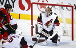 Arizona Coyotes goalie Cal Pickard, right, stops a shot from Calgary Flames' Mikael Backlund, of Sweden, during second period NHL hockey action in Calgary, Alberta, Monday, Feb. 18, 2019. (Jeff McIntosh/The Canadian Press via AP)