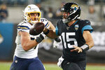Jacksonville Jaguars quarterback Gardner Minshew (15) scrambles away from Los Angeles Chargers defensive end Joey Bosa, left, as he looks for a receiver during the second half of an NFL football game, Sunday, Dec. 8, 2019, in Jacksonville, Fla. (AP Photo/Stephen B. Morton)