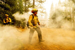Northern Sonoma County Fire District firefighters Erik Padilla, right, and Joe Young extinguish hot spots while protecting Lake Almanor West homes from the Dixie Fire on Thursday, Aug. 5, 2021, in Plumas County, Calif. They work out of the Geyserville Fire Station. (AP Photo/Noah Berger)
