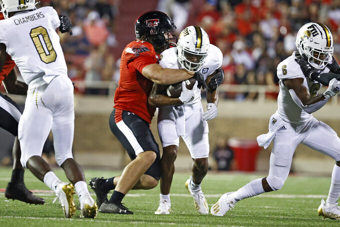 Texas Tech's Colin Schooler, center left, tackles Florida International's Bryce Singleton, center right, during the second half of an NCAA college football game on Saturday, Sept. 18, 2021, in Lubbock, Texas. (AP Photo/Brad Tollefson)
