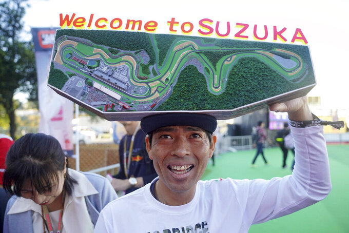 A fan with a decoration of Suzuka Circuit waits for drivers in front of the gate of the paddock ahead of the Japanese Formula One Grand Prix in Suzuka, central Japan, Sunday, Oct. 13, 2019. (AP Photo/Toru Hanai)