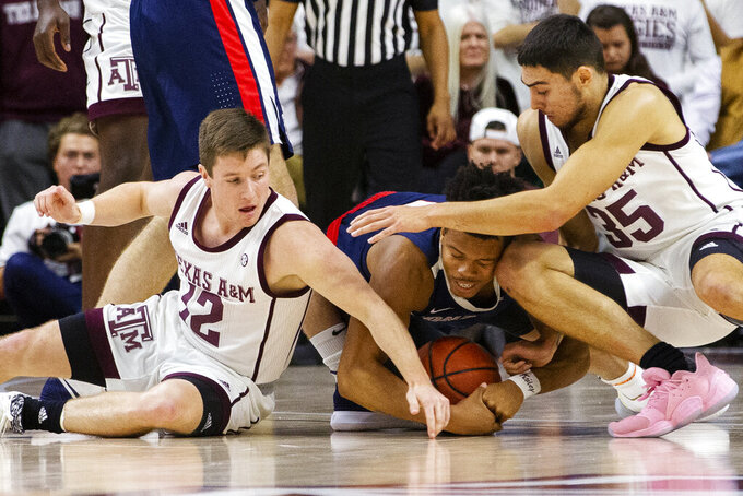 Gonzaga guard Admon Gilder (1) goes after a loose ball against Texas A&M guard Mark French (12) and Texas A&M forward Yavuz Gultekin (35) during the first half of an NCAA college basketball game Friday, Nov. 15, 2019, in College Station, Texas. (AP Photo/Sam Craft)