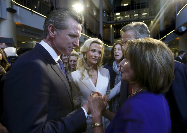 FILE - In this Jan. 7, 2019, file photo, California Gov. Gavin Newsom, left, talks with U.S. House Speaker Nancy Pelosi in Sacramento, Newsom has hung his hopes for avoiding drastic California budget cuts squarely on the federal government. His budget proposal Thursday, May 14, 2020 warned of $14 billion in cuts to public education and other areas if Congress doesn't approve more coronavirus-related funding.  (AP Photo/Rich Pedroncelli, File)