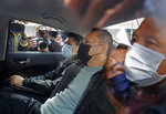 Former law professor Benny Tai, center, a key figure in Hong Kong's 2014 Occupy Central protests and also was one of the main organizers of the primaries, sits in a car after being arrested by police in Hong Kong, Wednesday, Jan. 6, 2021. About 50 Hong Kong pro-democracy figures were arrested by police on Wednesday under a national security law, following their involvement in an unofficial primary election last year held to increase their chances of controlling the legislature, according to local media reports. (AP Photo/Apple Daily)