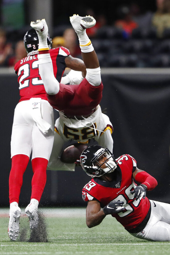 Atlanta Falcons defensive back Jayson Stanley (23) and Atlanta Falcons cornerback Taveze Calhoun (39) hit Washington Redskins wide receiver Cam Sims (89) during the second half an NFL preseason football game, Thursday, Aug. 22, 2019, in Atlanta. (AP Photo/John Bazemore)