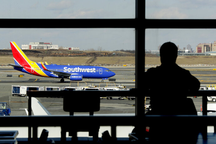 FILE- In this Jan. 25, 2019, file photo a Southwest Airlines jet moves on the runway as a person eats at a terminal restaurant at LaGuardia Airport in New York. The National Transportation Safety Board is meeting Tuesday, Nov. 19  in Washington to consider the cause of a deadly engine failure on a Southwest Airlines flight last year. The incident killed a passenger who was blown partly out of the plane when a piece of the engine shattered the window next to her. (AP Photo/Julio Cortez, File)