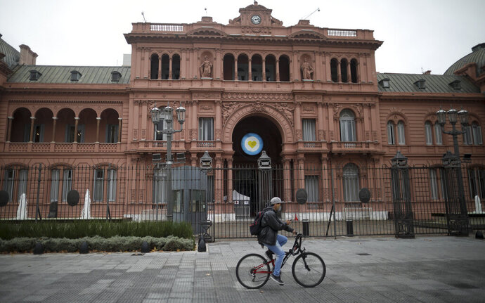 FILE - In this May 21, 2020, file photo, a man rides a bicycle in front of the government house during a government-ordered lockdown to curb the spread of COVID-19 in Buenos Aires, Argentina. Even amid a global pandemic, there's no sign that corruption is slowing down in Latin America. From Argentina to Panama, a number of officials have been forced to resign as reports of possibly fraudulent purchases of ventilators, masks and medical supplies proliferate. (AP Photo/Natacha Pisarenko, File)