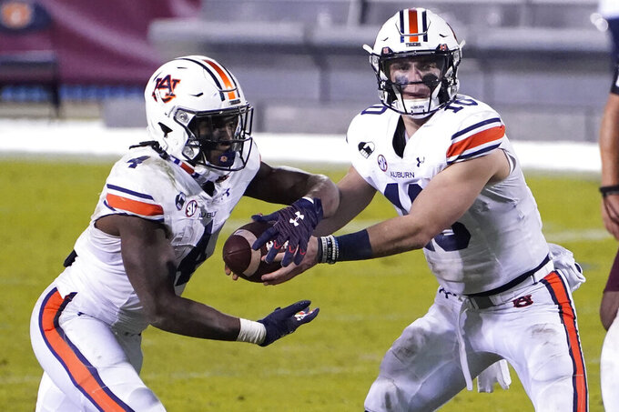 Auburn quarterback Bo Nix (10) hands off to running back Tank Bigsby (4) during the second half of the team's NCAA college football game against Mississippi State, Saturday, Dec. 12, 2020, in Starkville, Miss.  (AP Photo/Rogelio V. Solis)