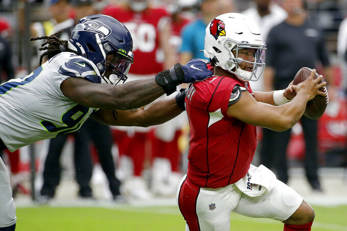 Arizona Cardinals quarterback Kyler Murray (1) eludes the reach of Seattle Seahawks outside linebacker Jadeveon Clowney (90) during the first half of an NFL football game, Sunday, Sept. 29, 2019, in Glendale, Ariz. (AP Photo/Rick Scuteri)