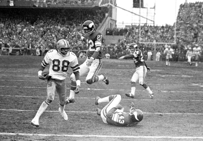 """FILE - In this Dec. 28, 1975, file photo, Dallas Cowboy wide receiver Drew Pearson (88) nears the end zone on a game-winning 50-yard touchdown pass play in the fourth quarter of an NFL football game against the Minnesota Vikings in Bloomington, Minn. Cowboys quarterback Roger Staubach explained his game-winning throw by saying, """"I closed my eyes and said a Hail Mary. Staubach and Pearson have connected again as part of a project to create a digital collectible of their famous Hail Mary for the Dallas Cowboys against Minnesota in 1975. It's part of an emerging product in sports memorabilia called non-fungible tokens, or NFTs. (AP Photo/File)"""
