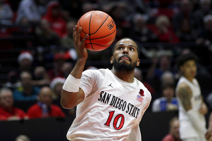 FILE - In this Dec. 18, 2019 file photo, San Diego State guard KJ Feagin during the second half of an NCAA college basketball game against San Diego Christian in San Diego. San Diego State basketball is the hottest ticket in town again. The undefeated Aztecs, who have climbed to No. 7 in The Associated Press poll, are playing as well as they did during their two Sweet 16 seasons during the last decade, including when Kawhi Leonard was the big star. This time it's a trio of transfers powering the Aztecs (15-0, 4-0 Mountain West Conference), who along with Auburn remain the nation's only undefeated teams. (AP Photo/Gregory Bull, File)
