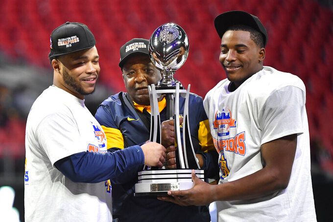 North Carolina A&T quarterback and offensive player of the game Kylil Carter, left, coach Sam Washington, and defensive player of the game linebacker Jacob Roberts, right, hold the trophy after the Celebration Bowl NCAA college football game against Alcorn State, Saturday, Dec. 21, 2019, in Atlanta. North Carolina A&T won 64-44. (John Amis/Atlanta Journal-Constitution via AP)