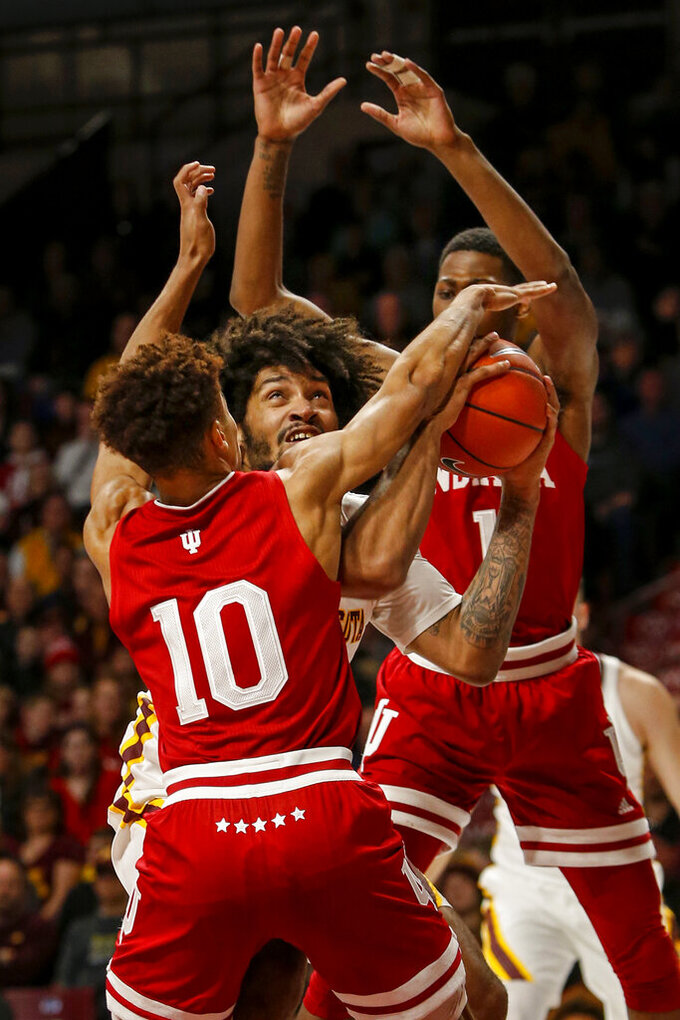 Minnesota's Jordan Murphy (3) looks to the basket as he moves between Indiana's Rob Phinisee (10) and Aljami Durham (1) in the first half of an NCAA college basketball game Saturday, Feb. 16, 2019, in Minneapolis. (AP Photo/Bruce Kluckhohn)