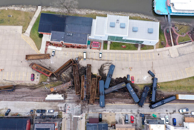 This aerial photo provided by the Scott County, Iowa, Emergency Management Agency shows a train derailment that sent at least a dozen rail cars and tankers off their tracks, the Friday, Jan. 3, 2020 , in downtown LeClaire, Iowa. The derailment, along U.S. Highway 67, just a couple of hundred feet from the banks of the Mississippi River, forced police to send a hazardous materials team to the site. (Scott County Emergency Management Agency via AP)