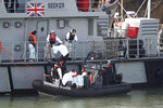 A group of people, thought to be migrants, disembark the deck of HMC Seeker, as they climb aboard a Border Force rib at Dover marina in Kent, England after a small boat incident in the English Channel, Tuesday Sept. 22, 2020. (Gareth Fuller/PA via AP)