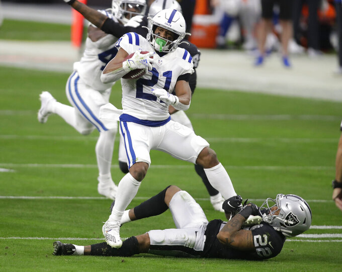 Indianapolis Colts running back Nyheim Hines (21) runs against Las Vegas Raiders cornerback Keisean Nixon (22) during the first half of an NFL football game, Sunday, Dec. 13, 2020, in Las Vegas. (AP Photo/Isaac Brekken)
