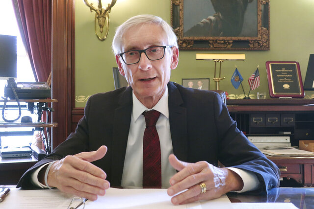FILE - In this Dec. 4, 2019 file photo, Wisconsin Gov. Tony Evers speaks during an interview with The Associated Press in his Statehouse office in Madison, Wis. Republican-controlled legislatures are increasingly trying to strip Democratic governors of their executive authority to close businesses and schools, a power grab that channels frustration over the economic toll of the coronavirus pandemic but could come with long-term consequences for how their states fight disease.  (AP Photo/Scott Bauer, File)