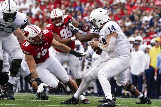 Penn State's Sean Clifford tries to get away from Wisconsin's Nick Herbig during the first half of an NCAA college football game Saturday, Sept. 4, 2021, in Madison, Wis. (AP Photo/Morry Gash)