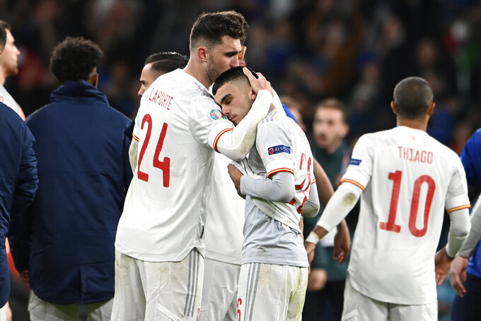 Spain's Aymeric Laporte, left, comforts Spain's Pedri after the Euro 2020 soccer championship semifinal match between Italy and Spain at Wembley Stadium in London, Tuesday, July 6, 2021. (Andy Rain/Pool via AP)