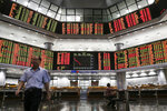 An investor walks in front of stock trading boards at a private stock market gallery in Kuala Lumpur, Malaysia, Thursday, May 2, 2019. Asian stocks were mixed on Thursday after the U.S. Federal Reserve kept its benchmark interest rate intact and steered clear of suggesting that a cut was possible this year. Trading was light as markets in Japan and mainland China were closed. (AP Photo/Annice Lyn)