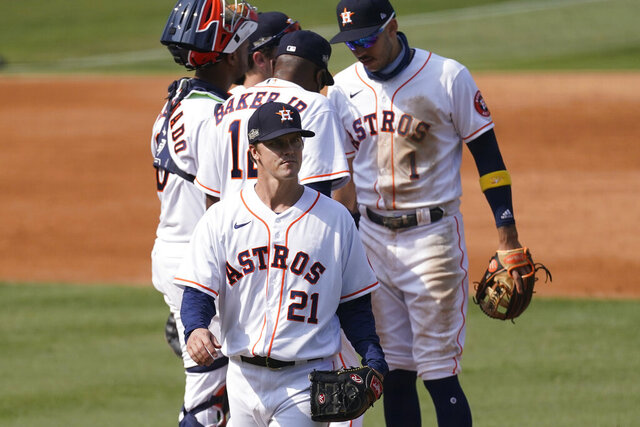 Houston Astros pitcher Zack Greinke (21) walks to the dugout after being taken out for a relief pitcher by manager Dusty Baker Jr., center, during the fifth inning of Game 4 of a baseball American League Division Series against the Oakland Athletics in Los Angeles, Thursday, Oct. 8, 2020. (AP Photo/Ashley Landis)