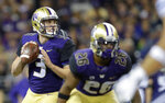 Washington quarterback Jake Browning looks to pass behind running back Salvon Ahmed during the second half of an NCAA college football game against BYU, Saturday, Sept. 29, 2018, in Seattle. (AP Photo/Ted S. Warren)