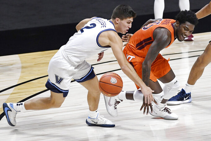 Villanova's Collin Gillespie, left, knocks the ball from Virginia Tech's Tyrece Radford during the first half of an NCAA college basketball game Saturday, Nov. 28, 2020, in Uncasville, Conn. (AP Photo/Jessica Hill)
