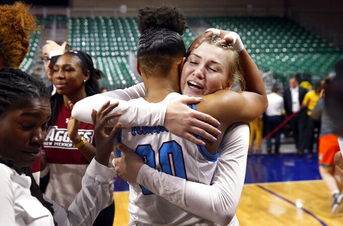 New Mexico State guard Gia Pack, left, (30) and teammate Brooke Salas (2) celebrate after the team beat Texas-Rio Grande Valley 76-73 in double overtime during a NCAA college basketball Western Athletic Conference Women's Tournament championship game Saturday, March 16, 2019, in Las Vegas. (AP Photo/Steve Marcus)