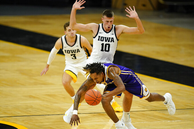 Western Illinois guard Anthony Jones is fouled by Iowa guard Joe Wieskamp (10) during the first half of an NCAA college basketball game, Thursday, Dec. 3, 2020, in Iowa City, Iowa. (AP Photo/Charlie Neibergall)