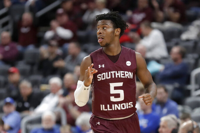 Southern Illinois' Lance Jones celebrates after making a 3-point basket during the first half of an NCAA college basketball game against Bradley in the quarterfinal round of the Missouri Valley Conference men's tournament Friday, March 6, 2020, in St. Louis. (AP Photo/Jeff Roberson)