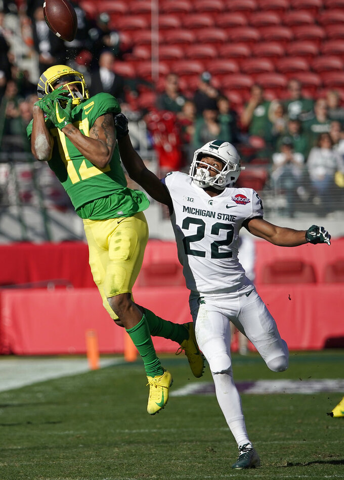 Oregon wide receiver Dillon Mitchell (13) cannot make a catch against Michigan State cornerback Josiah Scott (22) during the first half of the Redbox Bowl NCAA college football game Monday, Dec. 31, 2018, in Santa Clara, Calif. (AP Photo/Tony Avelar)