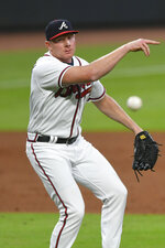 Atlanta Braves pitcher Mark Melancon turns a double play by throwing a ground ball by Miami Marlins' Matt Joyce to first base during the ninth inning of a baseball game Monday, Sept. 21, 2020, in Atlanta. Monte Harrison was tagged out at third base. (AP Photo/John Amis)