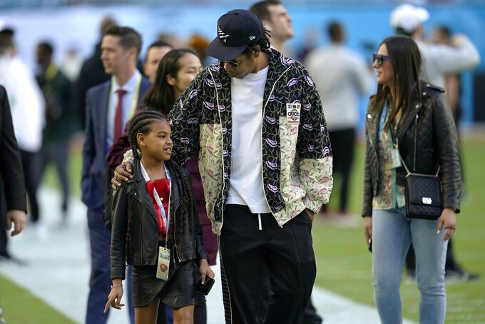 Entertainer Jay-Z speaks with his daughter Blue Ivy Carter as they arrive for the NFL Super Bowl 54 football game between the San Francisco 49ers and the Kansas City Chiefs, Sunday, Feb. 2, 2020, in Miami. (AP Photo/David J. Phillip)