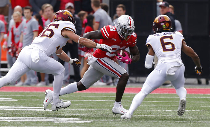Ohio State receiver Parris Campbell, center, looks for an opening between Minnesota linebacker Blake Cashman, left, and defensive back Chris Williamson during the first half of an NCAA college football game Saturday, Oct. 13, 2018, in Columbus, Ohio. (AP Photo/Jay LaPrete)