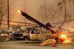 A utility pole burns as the Dixie Fire tears through the Greenville community of Plumas County, Calif., on Wednesday, Aug. 4, 2021. The fire leveled multiple historic buildings and dozens of homes in central Greenville. (AP Photo/Noah Berger)