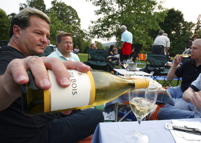 FILE - In this July 7, 2006 file photo, Michael Van Parks, left, pours wine with friends, Bill Beeman, center, and Don Usher, right, all of West Hartford, Conn., while having a picnic on the lawn at Tanglewood in Lenox, Mass. before the start of Boston Symphony Orchestra's opening night. The Boston Symphony Orchestra announced Friday, March 19, 2021 that its 2021 outdoor season at Tanglewood, the acclaimed symphony's summer home in the Berkshires of western Massachusetts, will feature a return to live, in-person concerts from July 9 to Aug. 16. The event was canceled in 2020 due to the COVID-19 pandemic. (AP Photo/Michael Dwyer, File)