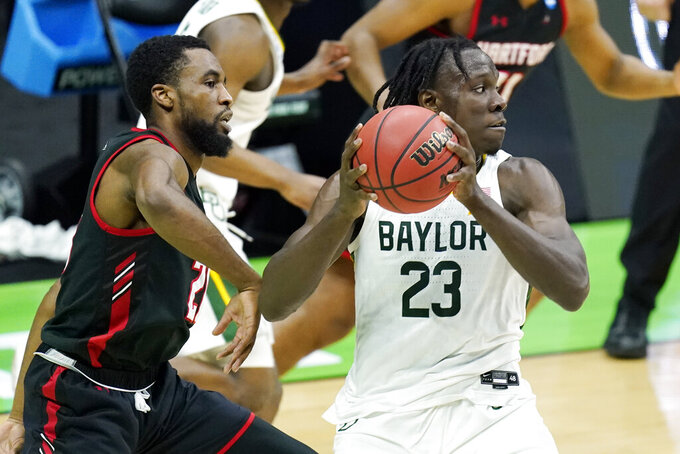 Baylor's Jonathan Tchamwa Tchatchoua (23) grabs a rebound in front of Hartford's Austin Williams, left, during the first half of a college basketball game in the first round of the NCAA tournament at Lucas Oil Stadium in Indianapolis Friday, March 19, 2021, in Indianapolis, Tenn. (AP Photo/Mark Humphrey)