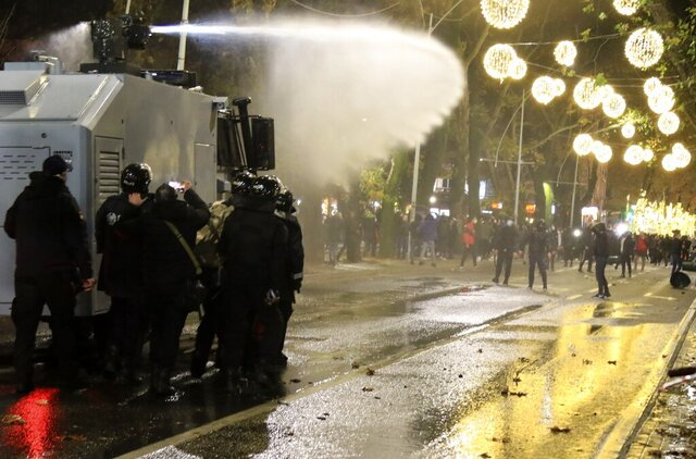 Albanian police use a water cannon against protesters during clashes in Tirana, Thursday, Dec. 10, 2020. Albanian protesters on Thursday renewed clashes with police over the fatal police shooting of a man during curfew hours despite the call from the authorities to respect a pandemic ban on public gatherings. (AP Photo/Hektor Pustina)